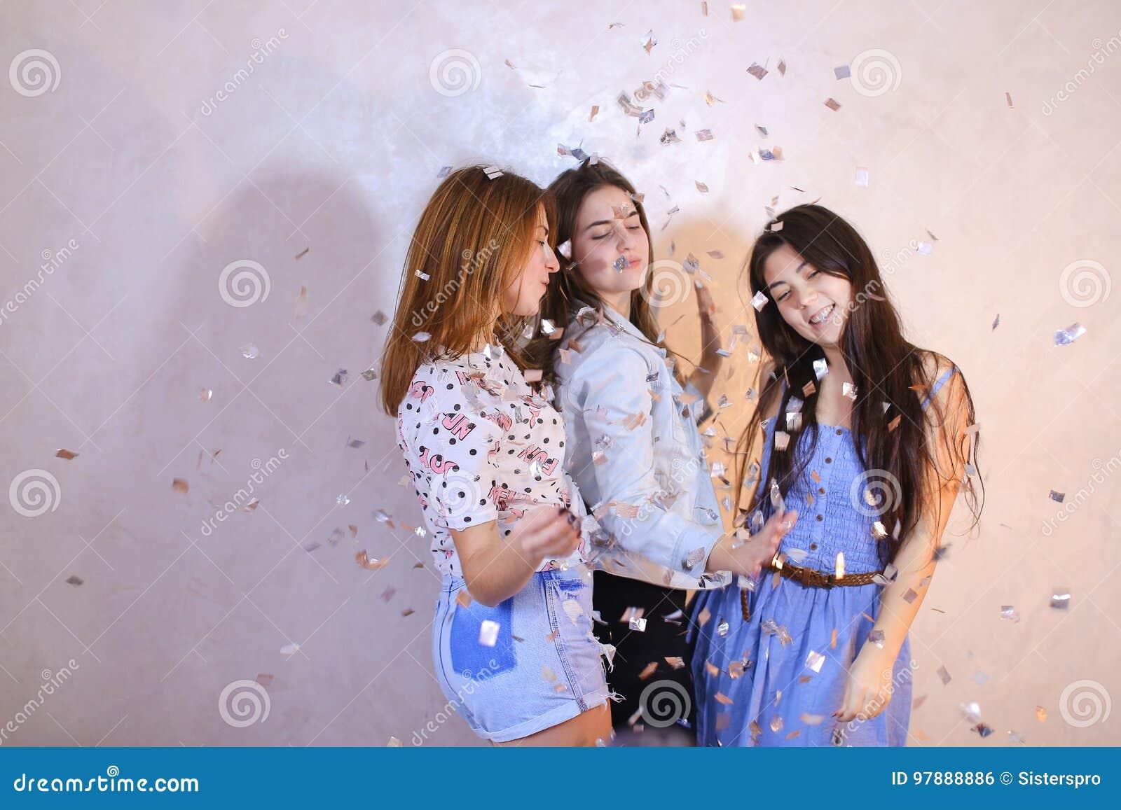 Śmieszna dziewczyny poza w kamerze z uśmiechami na ich stojaku i twarzach