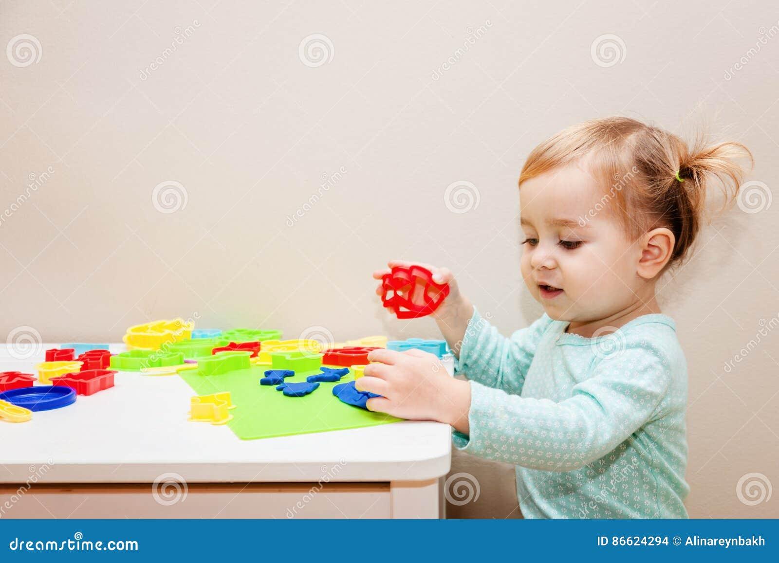Śmieszna jeden rok dziewczyna ma zabawę z modelarskim ciastem przy daycare