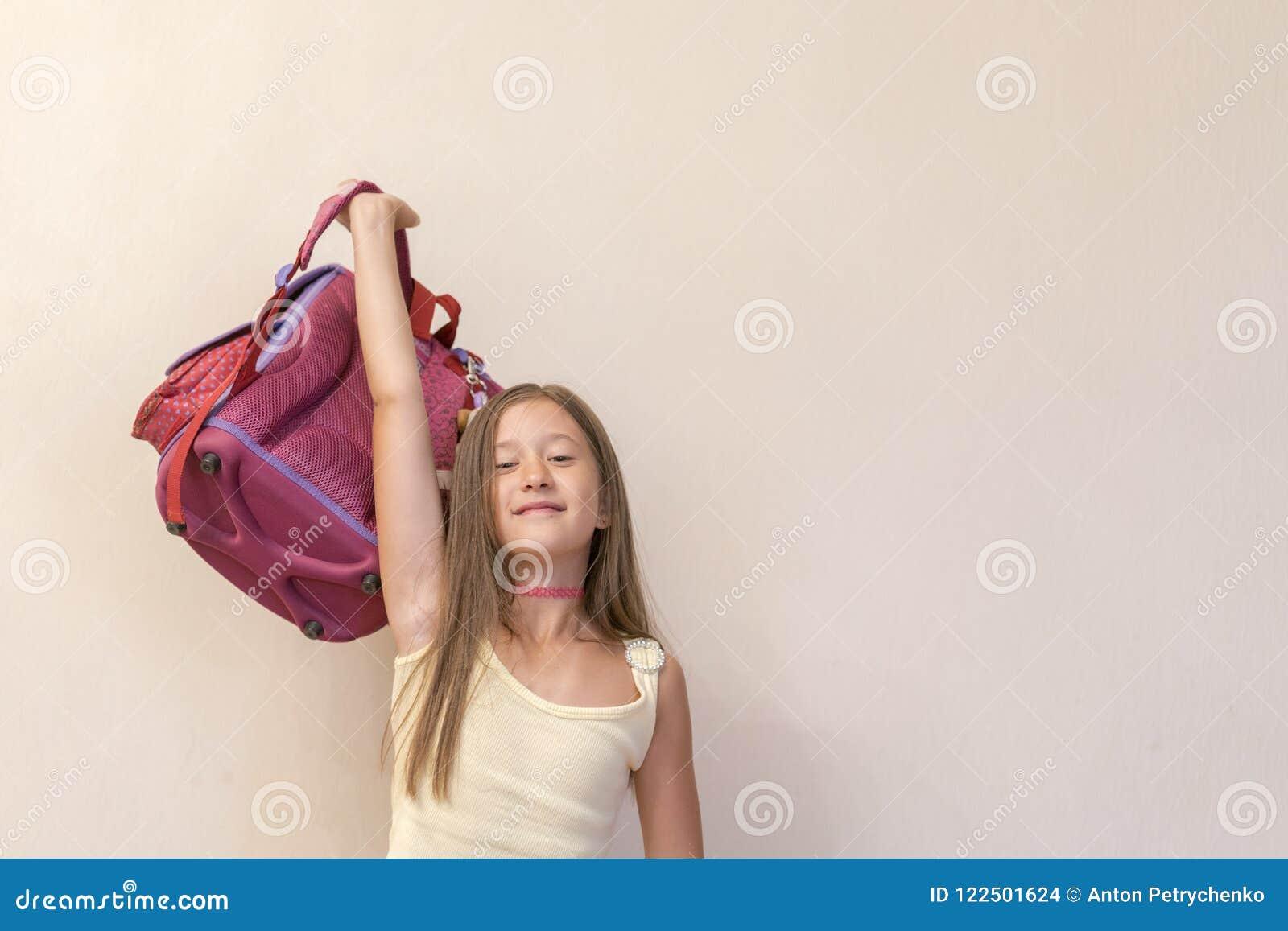 Śmieszna mała dziewczynka z dużym plecaka doskakiwaniem mieć przeciw biel ścianie zabawą i czarnych tła pojęcia do copyspace ksią