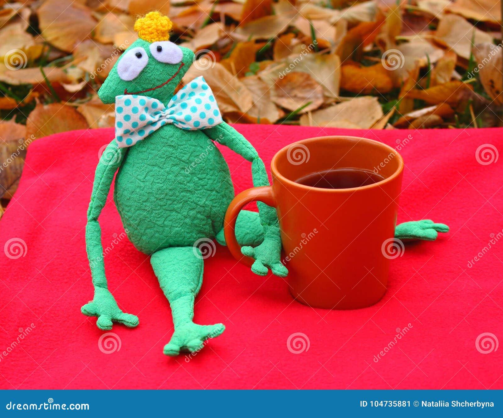 Śmieszna miękkiej części zabawki książe żaba z filiżanką herbata czeka na czerwonym chodniku, spadać liściach i