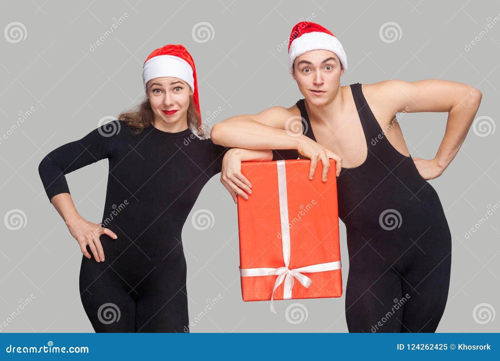 Śmieszna para w czerni smokingowych i czerwonych bożych narodzeń mienia prezenta kapeluszowym b