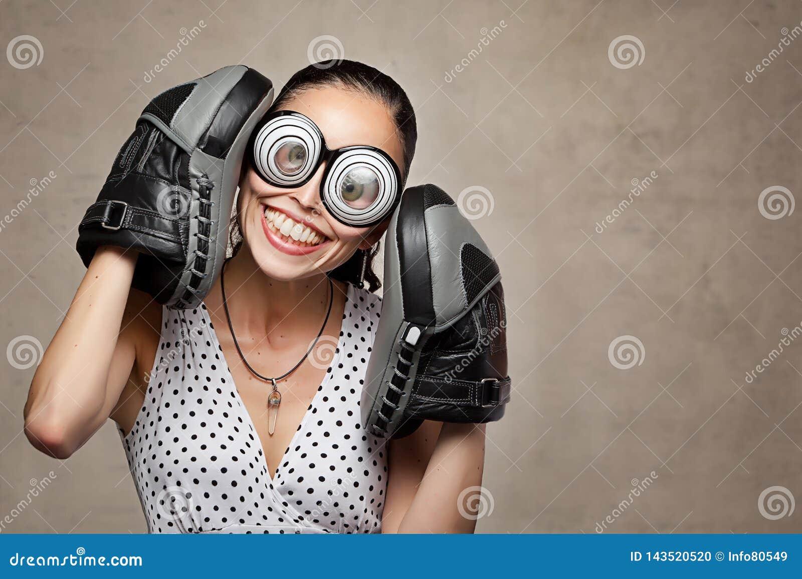 Śmieszna szalona kobieta z dużymi oczami, szkłami i bokserskimi rękawiczkami,