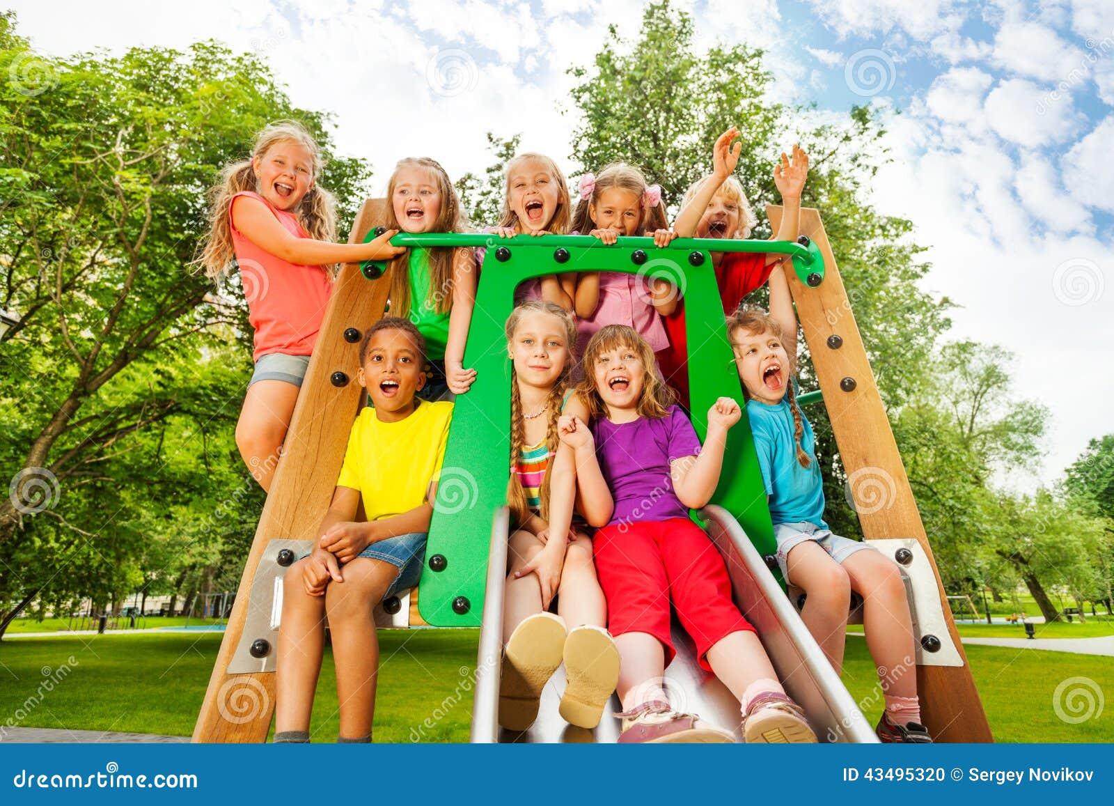 Śmieszni dzieci na boiska korytku z rękami up