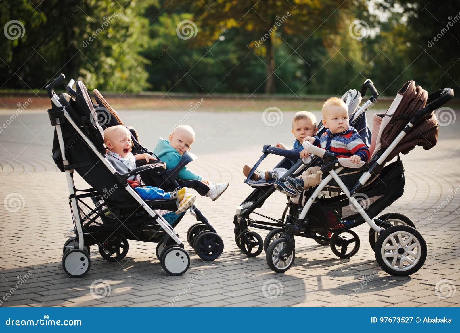 Śmieszni dzieci siedzi w spacerowiczach w parku