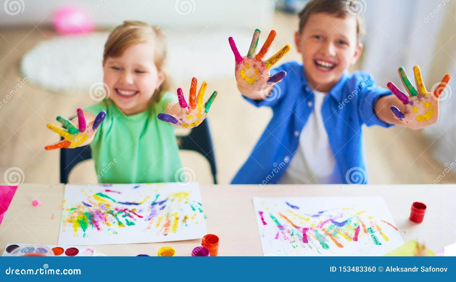 Śmieszni dzieciaki pokazują ich palmom malującą farbę kreatywnie klas sztuki piękne dwa dziecka chłopiec i dziewczyna śmiech Sele