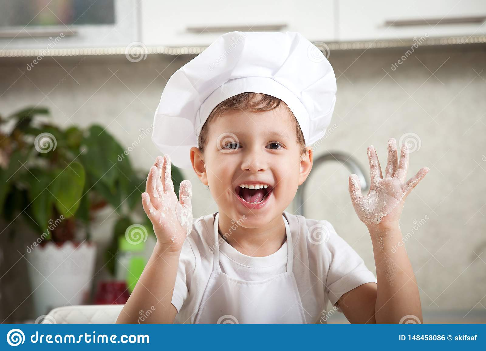 Śmieszny dziecko z mąką, szczęśliwa emocjonalna chłopiec ono uśmiecha się szczęśliwie