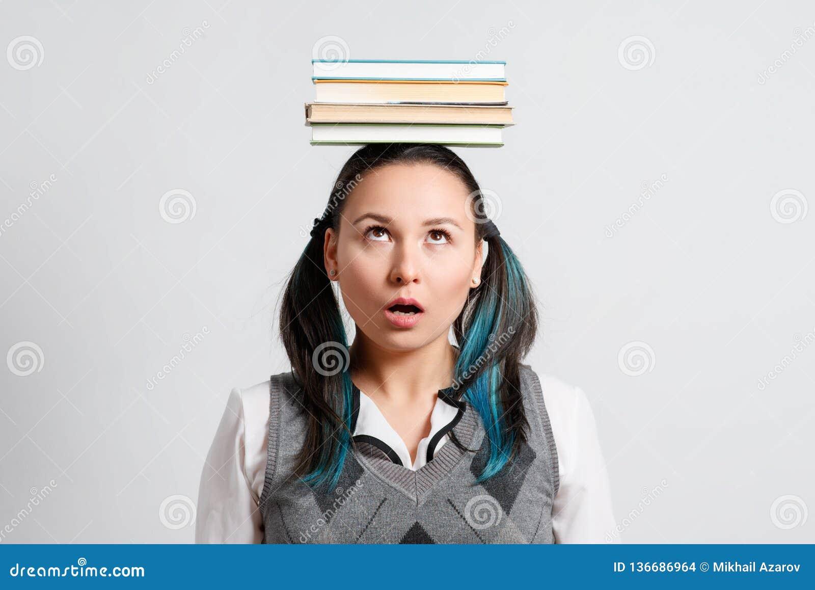 Śmieszny dziewczyna uczeń z stertą książki na ona kierownicza