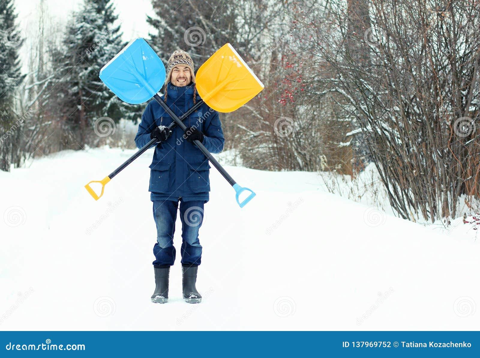 Śmieszny młody człowiek trzyma dwa śnieżnej łopaty, tworzy symbol Byczy Roger Zimy sezonowy pojęcie