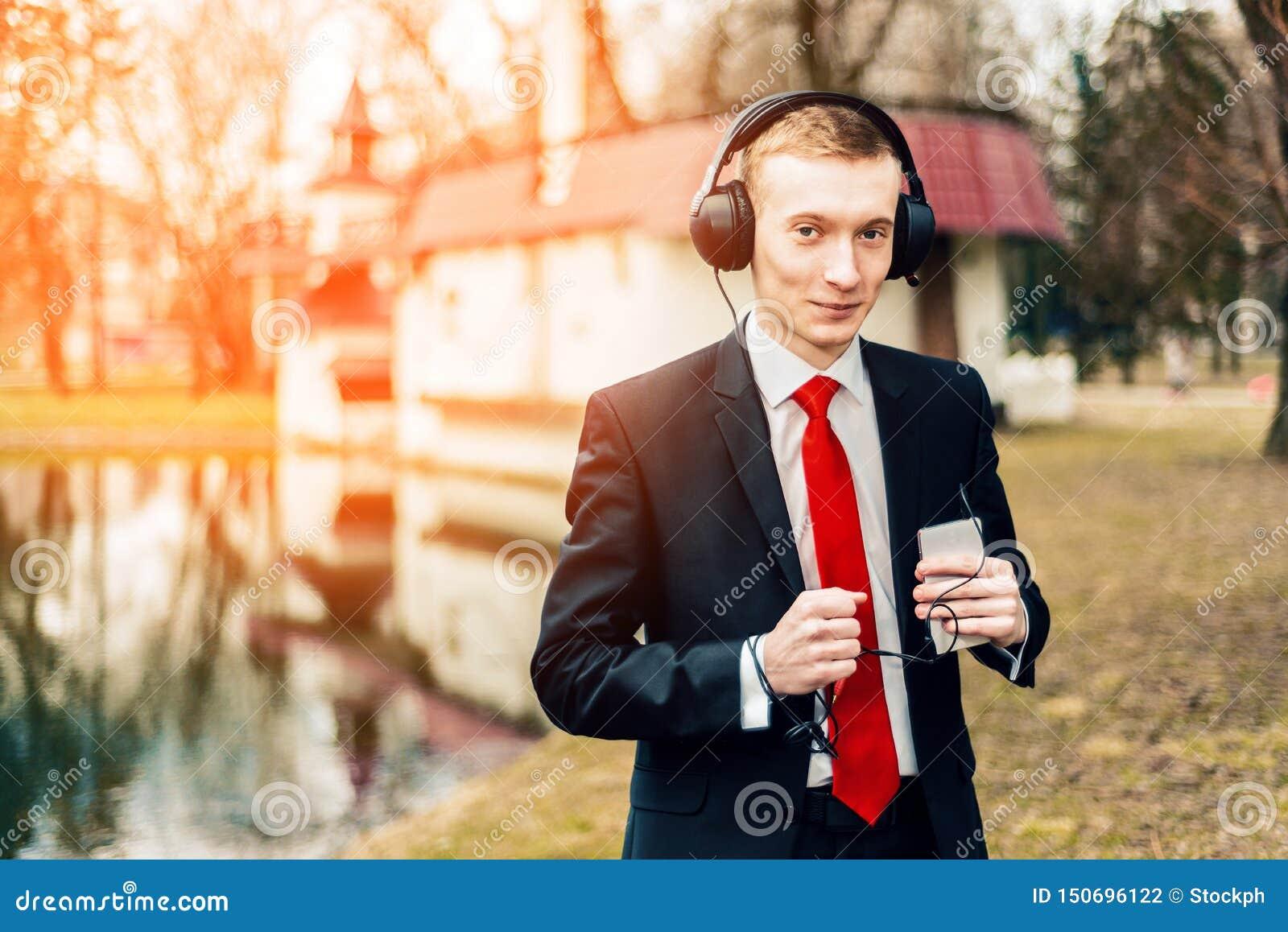 Śmieszny młody facet słucha muzyka z dużymi hełmofonami mężczyzna w czarnym kostiumu czerwonym krawacie i biznesmen odpoczywa, re