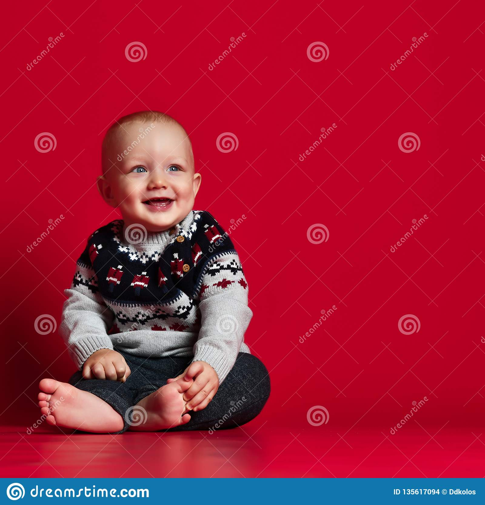 Śmieszny mały dziecko jest ubranym ciepłego trykotowego Bożenarodzeniowego pulower przy studiiem na zimnym zima dniu