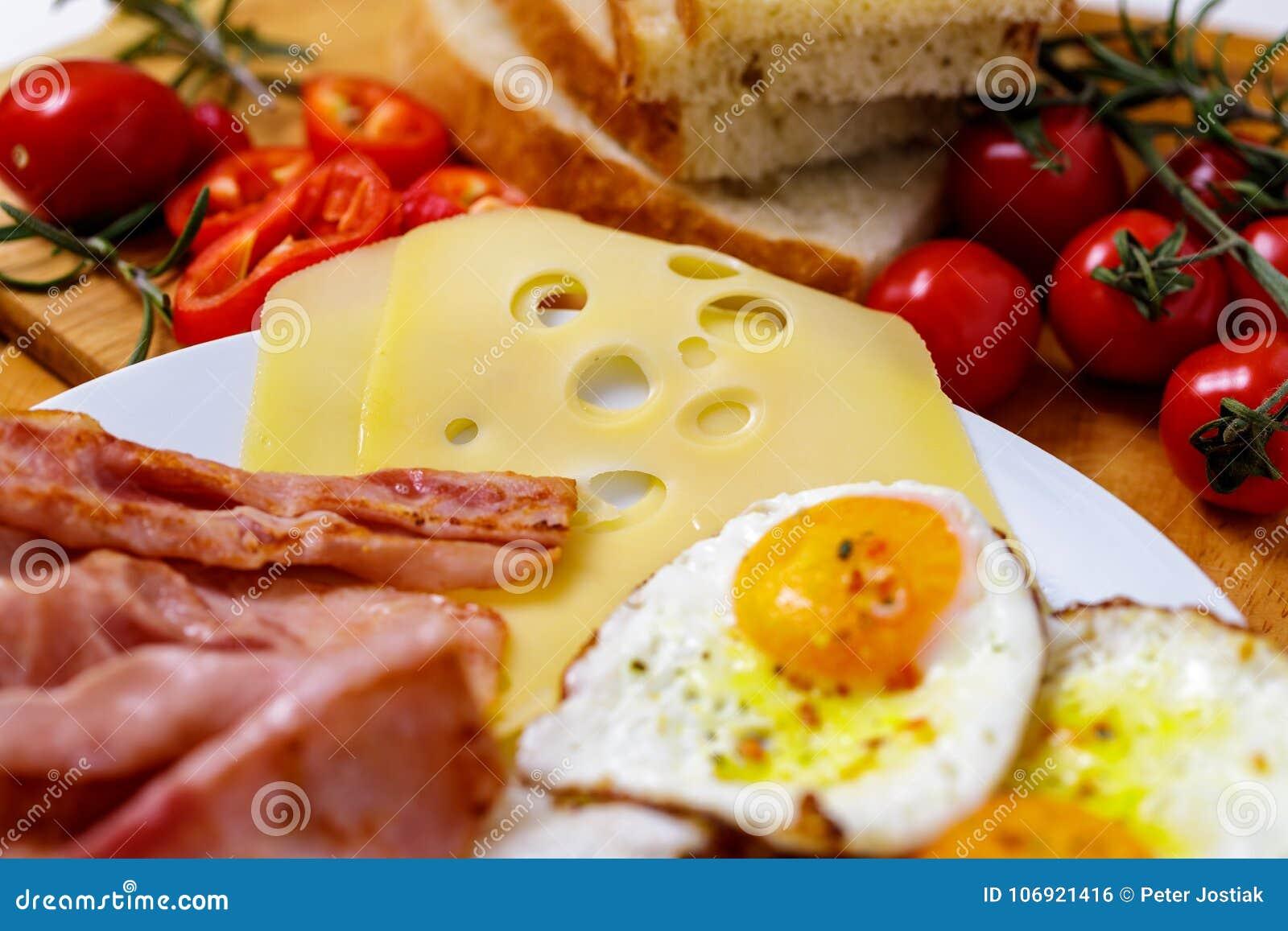 Śniadania smażący jajko, chleb, pomidory, baleron i pieprz na drewno stole,