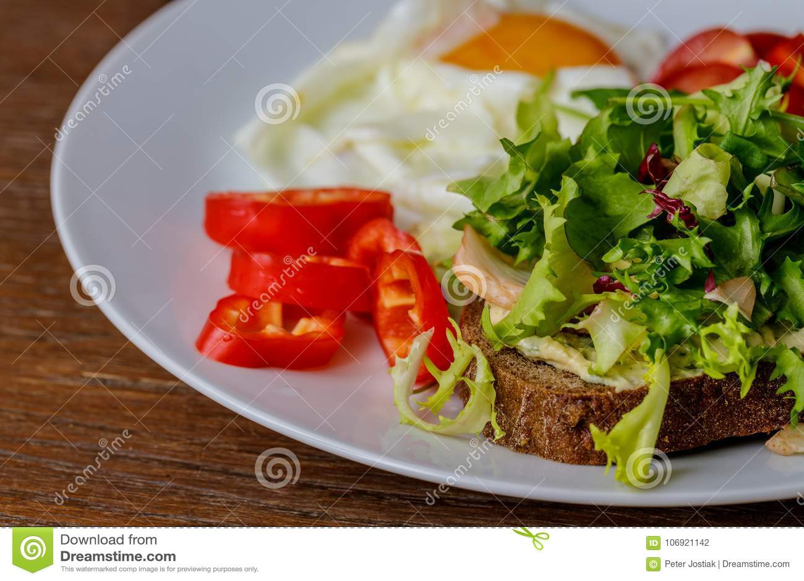 Śniadania smażący jajko, chleb, pomidory, hummus, pieprz i rucola na drewno stole,