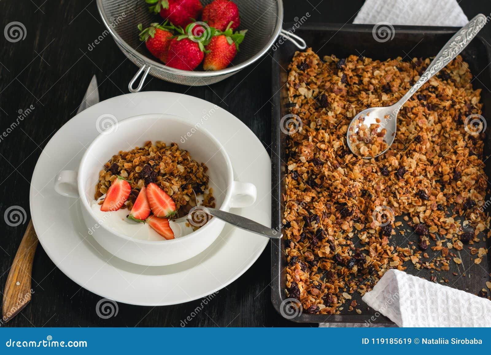 Śniadanie granola, jogurt i truskawki na zmroku stole,