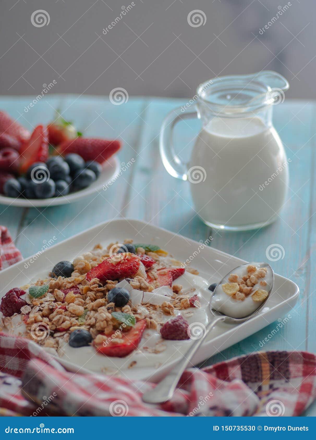 Śniadaniowy granola jogurt, truskawka, czarne jagody, malinki na białym talerzu