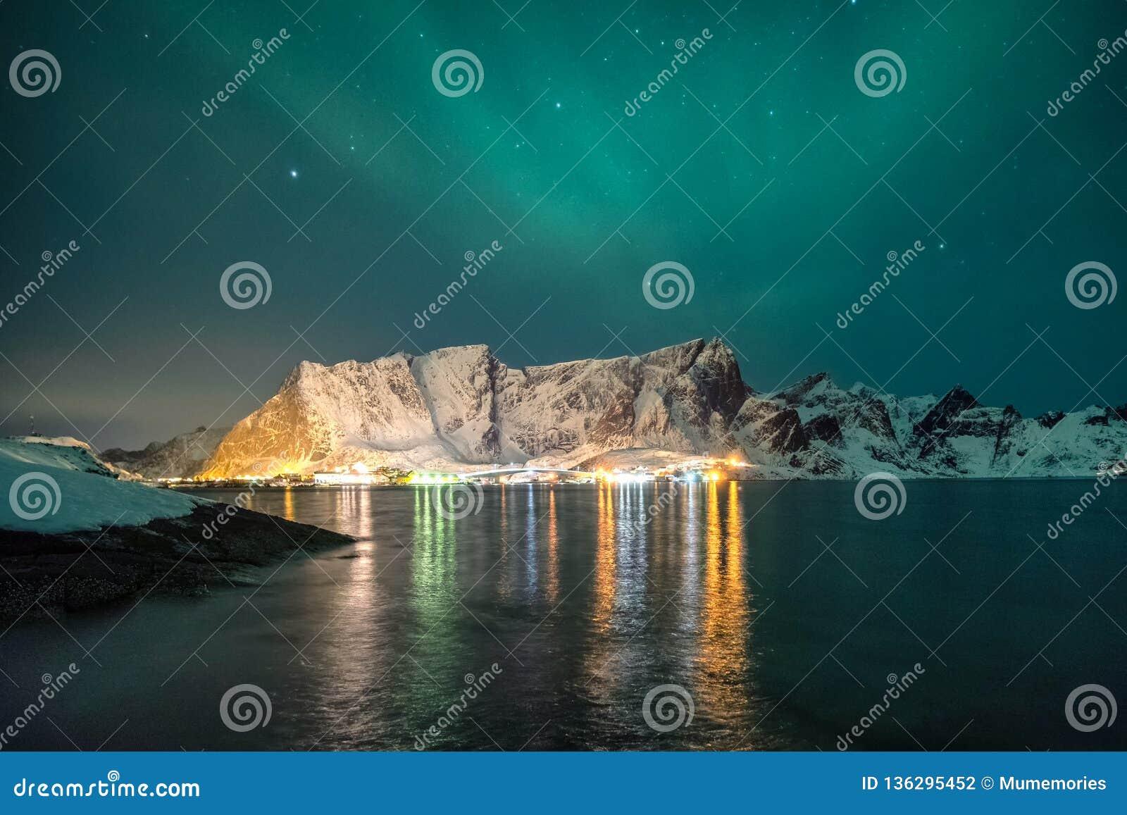 Śnieżny pasmo górskie z aurora borealis i olśniewającym miastem