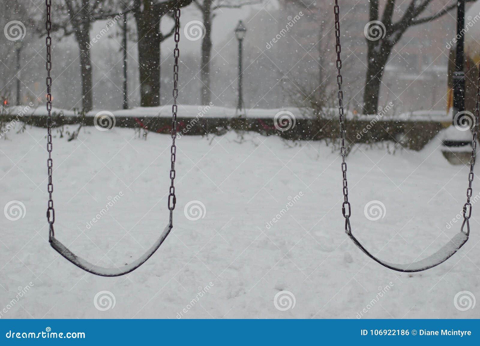 Śnieg spada na pustych huśtawkach w opustoszałym parku Jest jest zimny, niesamowity i obskurny