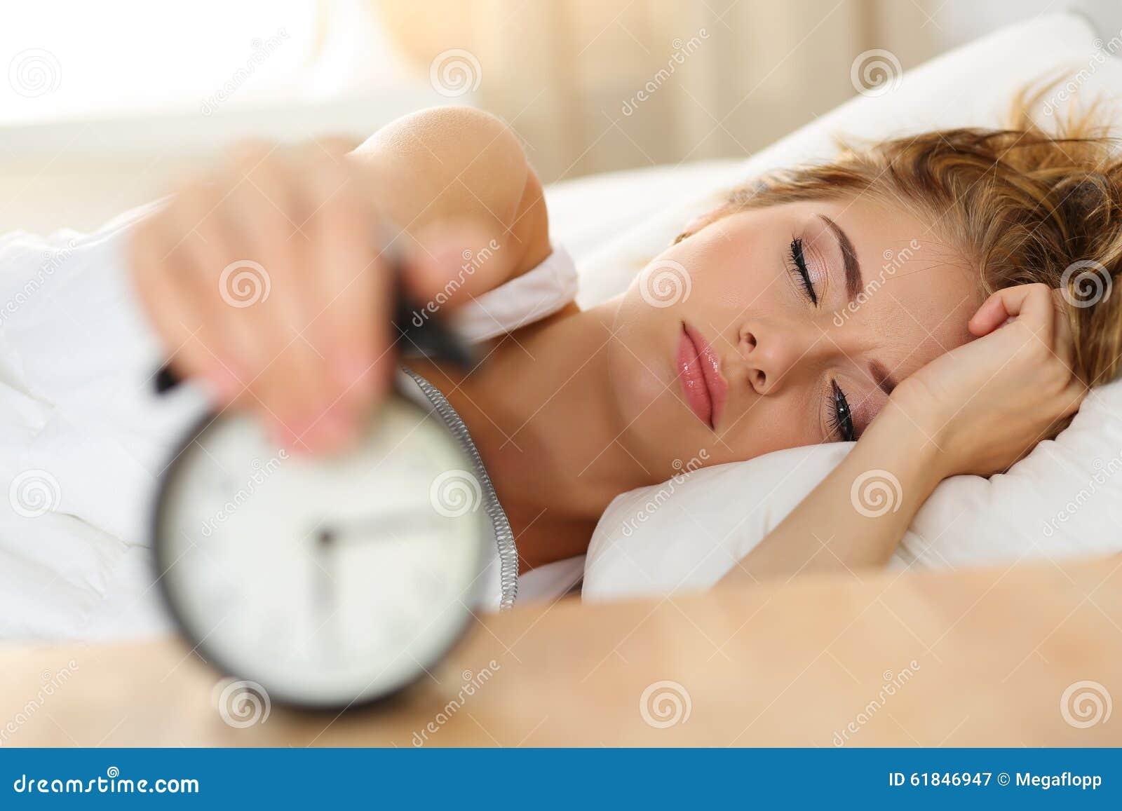 Śpiąca młoda kobieta próbuje zwłoka budzika