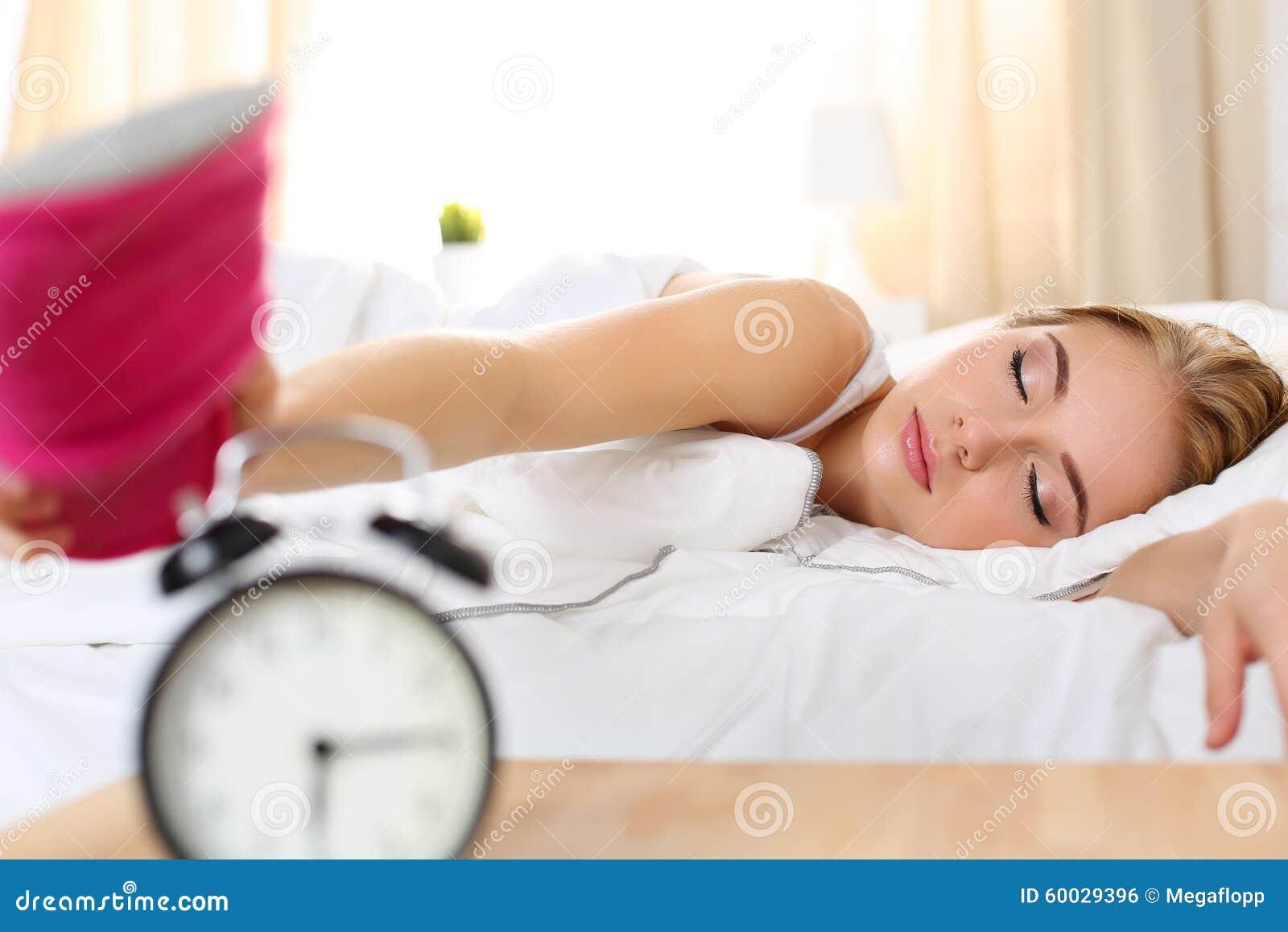 Śpiąca młoda piękna kobieta próbuje zwłoka budzika