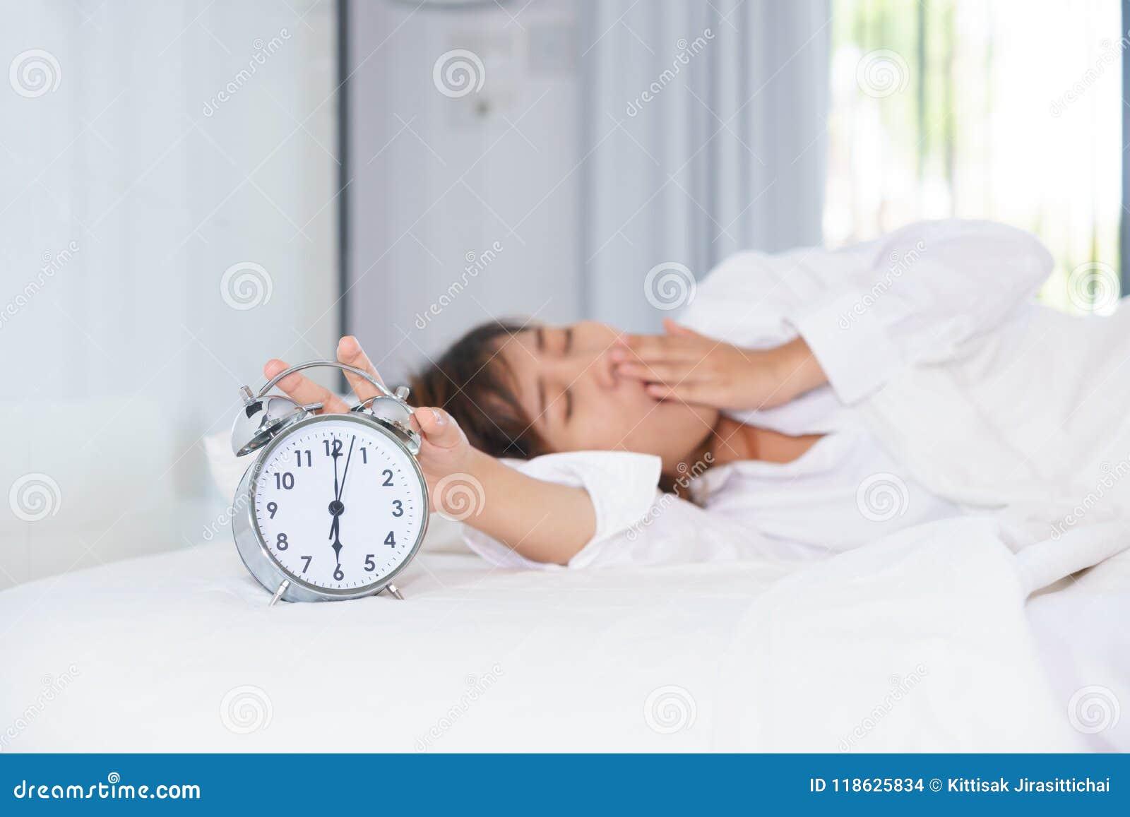 Śpiąca młodej kobiety rozciągania ręka próbować zwłoka budzika wewnątrz
