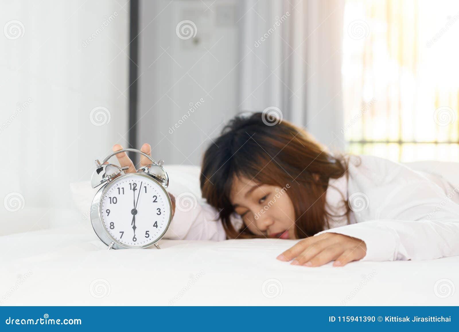 Śpiący kobiety próbować obraca daleko budzika w ranku