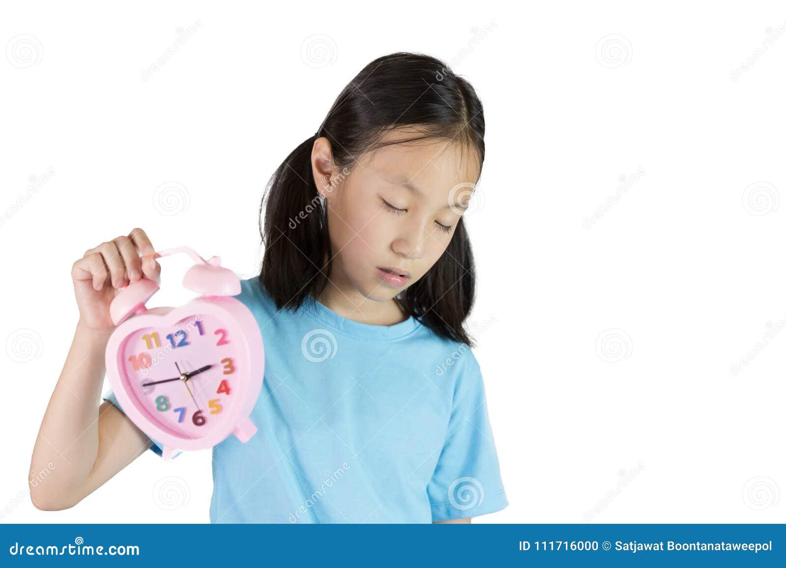 Śpiący portret azjatykci dziewczyny mienia zegar odizolowywający na białych półdupkach