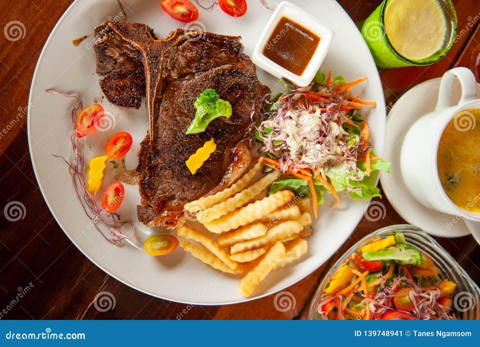 Średni rzadki Piec na grillu kość stek z sałatką, francuzów dłoniakami, pomidorami, puree ziemniaczane i piec szpinakami z serem