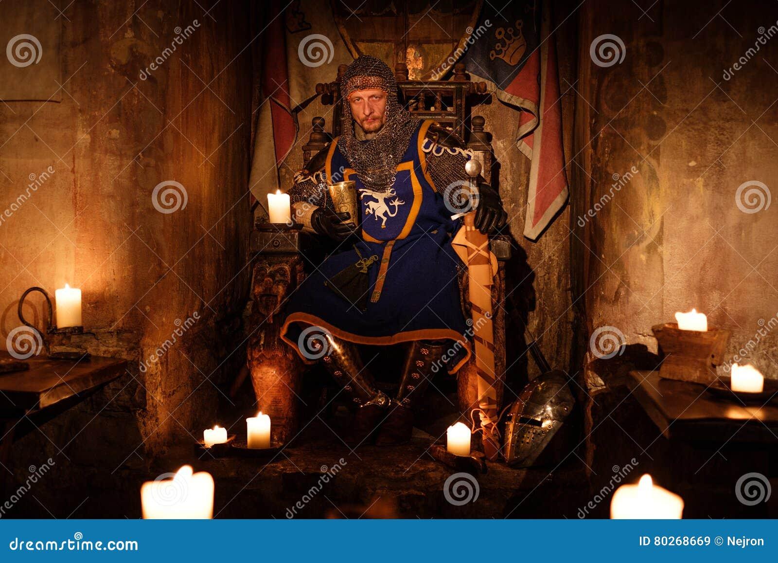 Średniowieczny królewiątko na tronie w antycznym grodowym wnętrzu