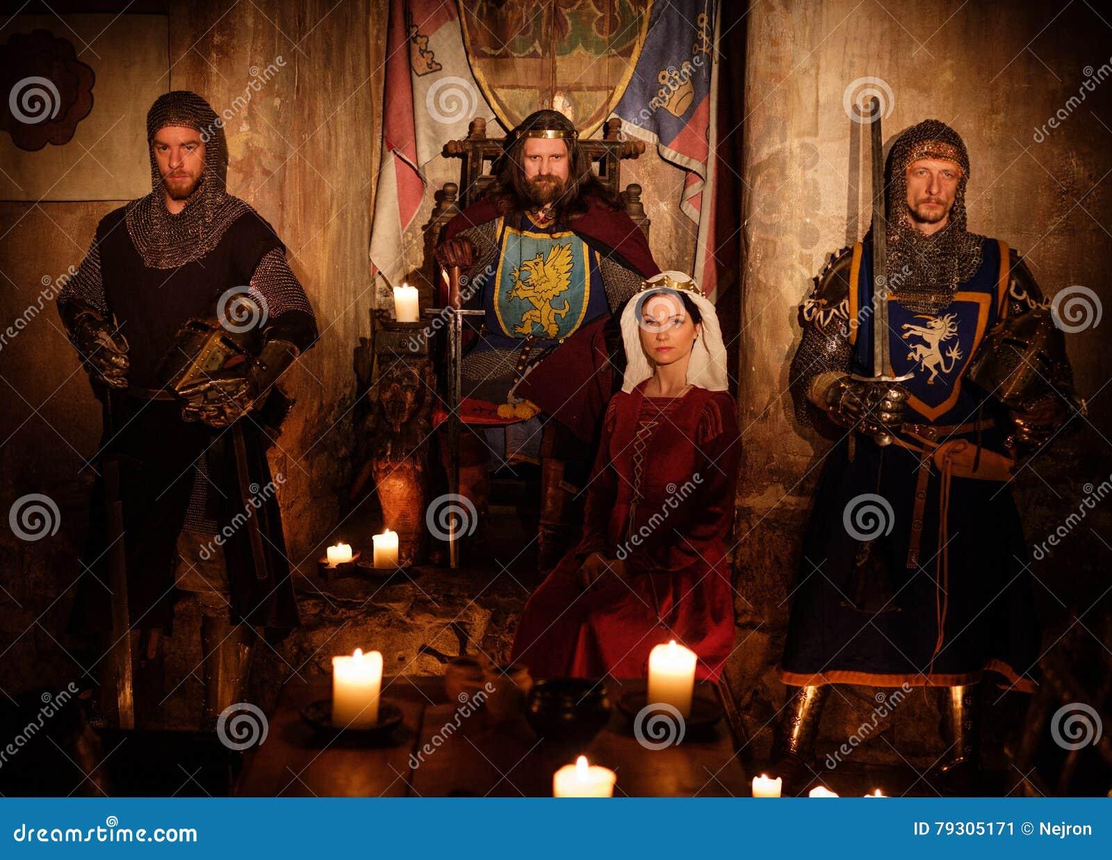 Średniowieczny królewiątko z jego rycerzami na strażniku w antycznym grodowym wnętrzu i królową
