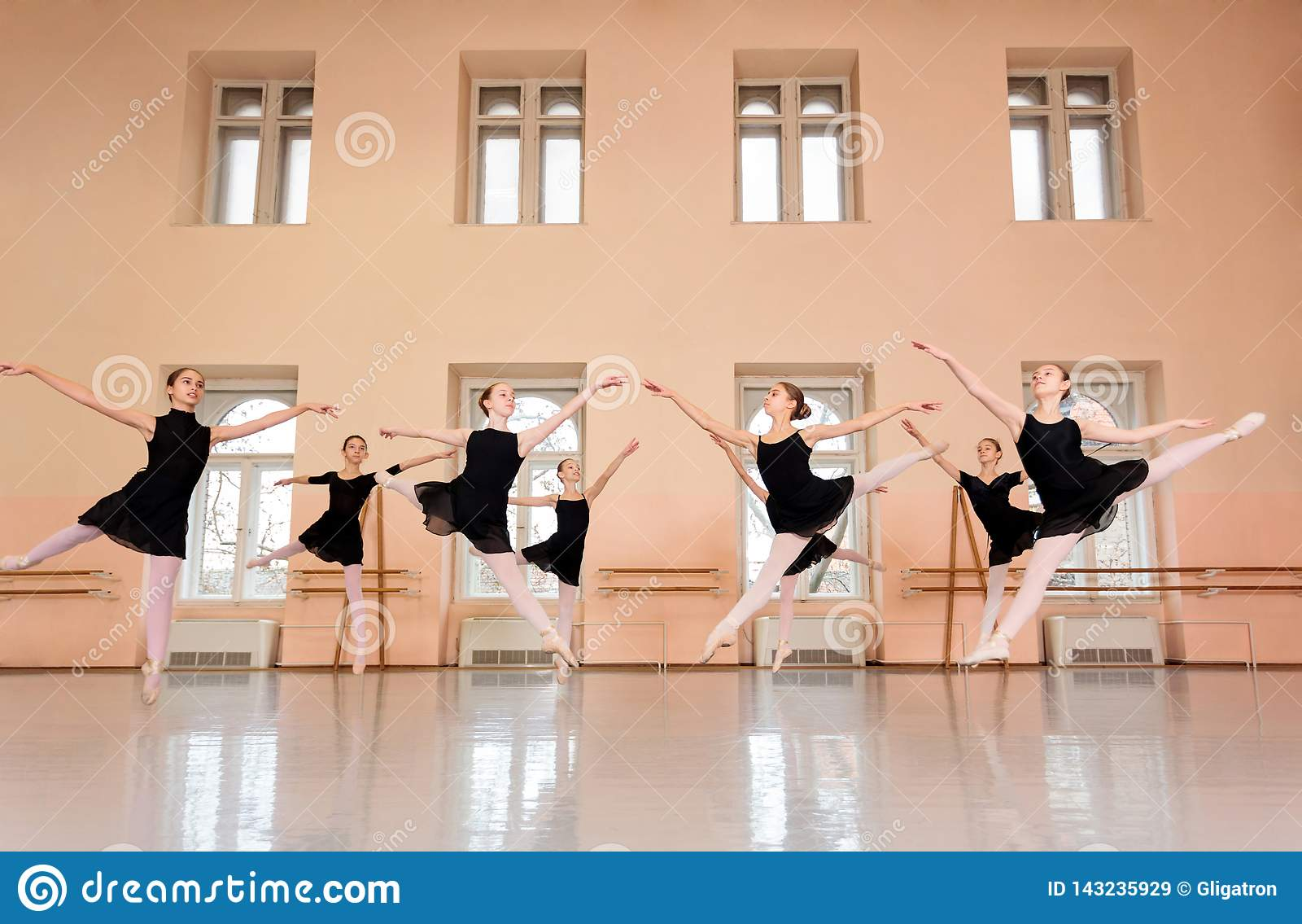 Środek grupa nastoletnie dziewczyny ćwiczy klasycznego balet w wielkim dancingowym studiu