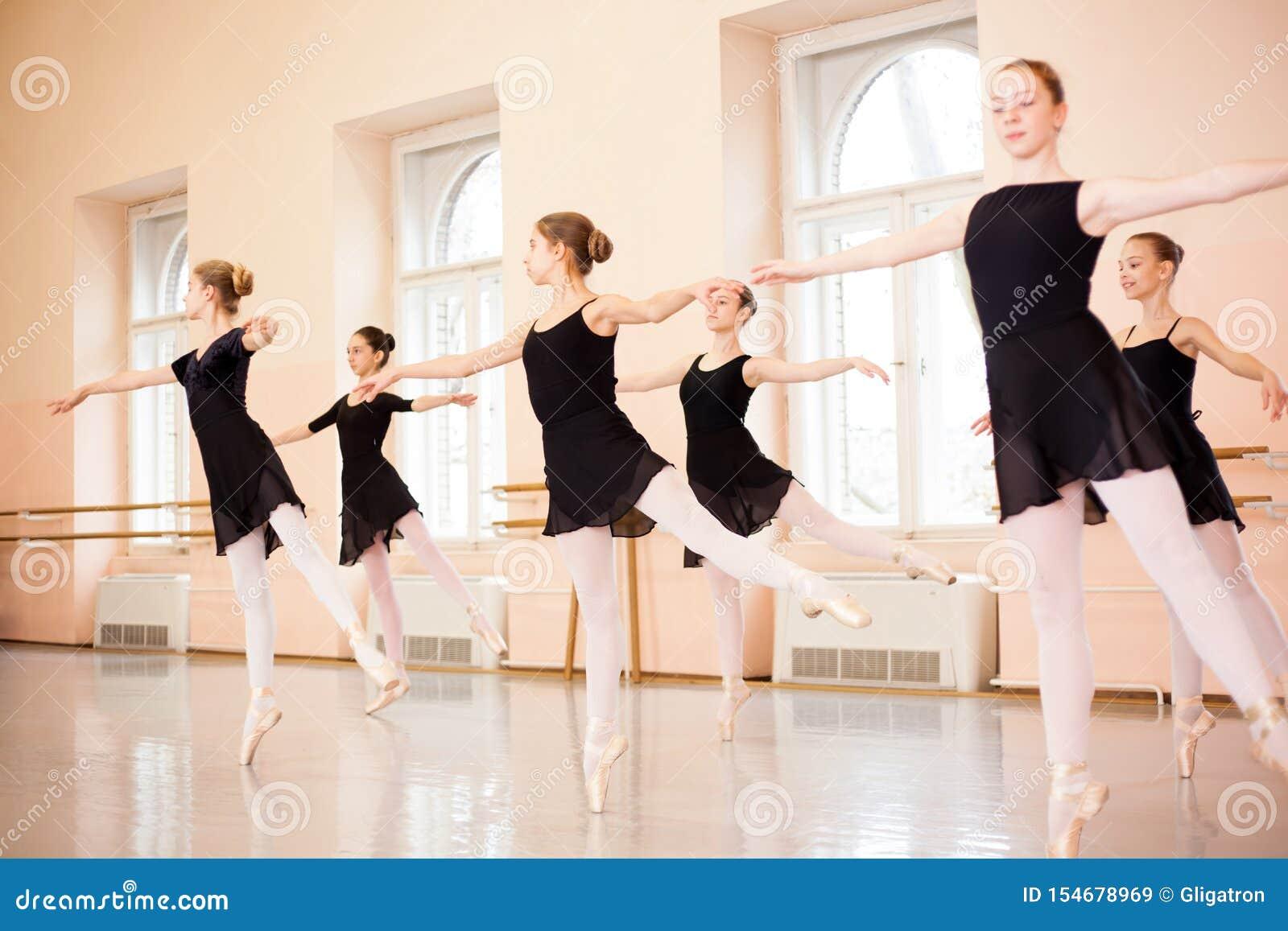 Środek grupa nastoletnie dziewczyny w czarnych sukniach ćwiczy baletniczych ruchy w wielkim tana studiu