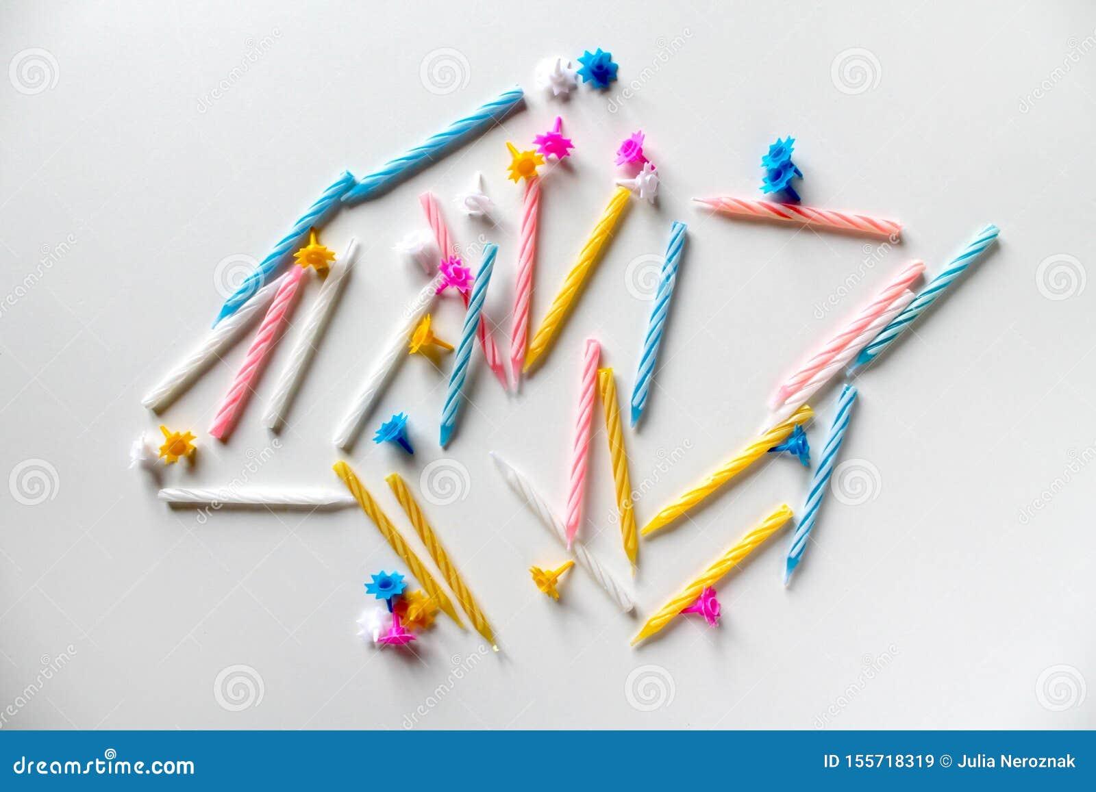 Świąteczny tło z jaskrawymi kolorowymi urodzinowymi świeczkami na białym tle
