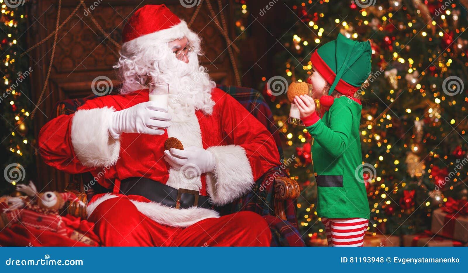 Święty Mikołaj i elfa dziecko w łasowania Bożenarodzeniowych pije dojnych ciastkach