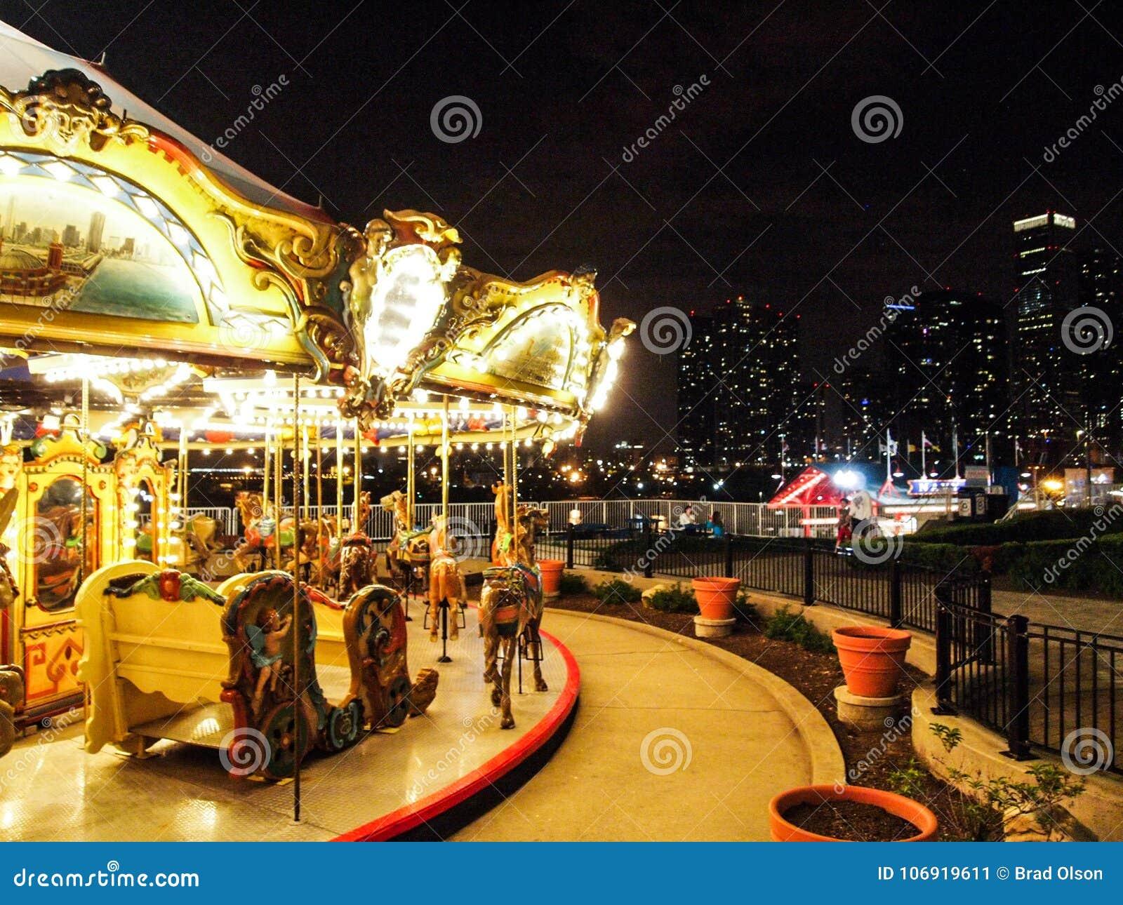 Światła parka rozrywki Karnawałowy wesoło iść round z nocy światłami miasto linia horyzontu w tle
