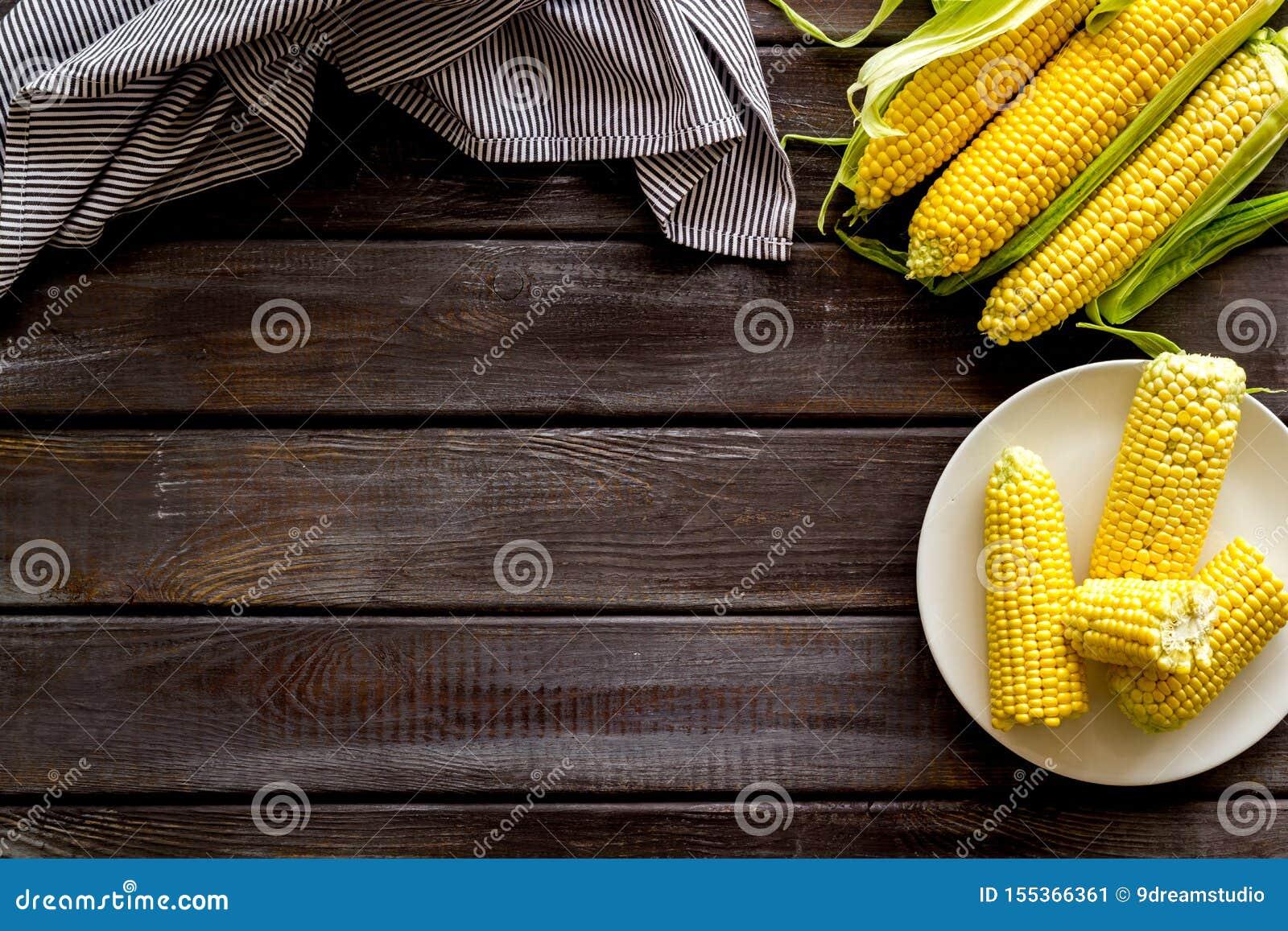 Świeża kukurudza na talerzu jako rolny jedzenie na drewnianej tło odgórnego widoku przestrzeni dla teksta