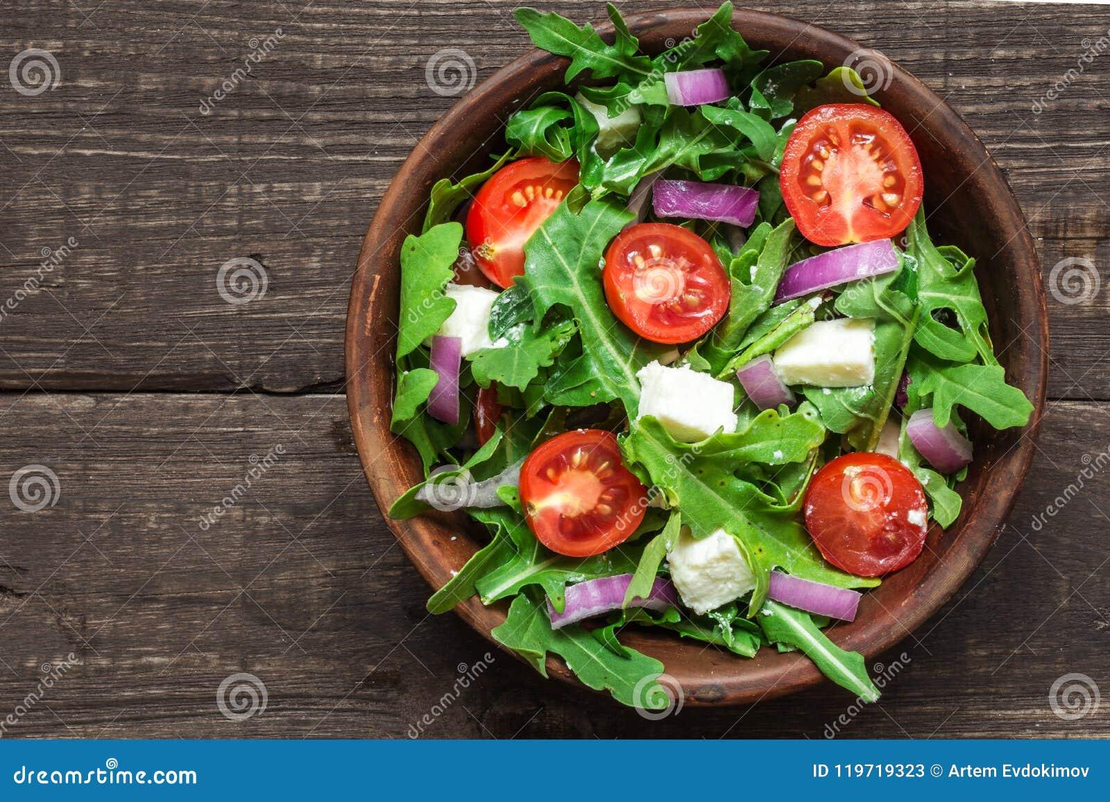 Świeża mixd sałatka z rucola, pomidorami wiśnia, feta serem i czerwoną cebulą w pucharze na nieociosanym drewnianym stole, Odgórn