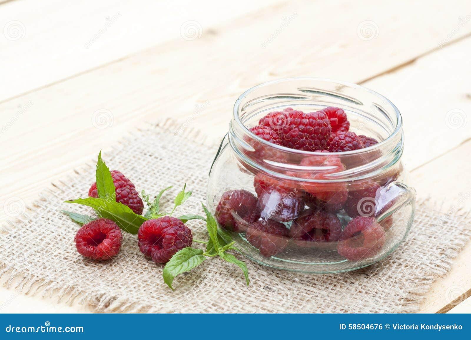 Świeża słodka czerwona malinka w szklanej mennicie na lekkim drewnianym stole i słoju