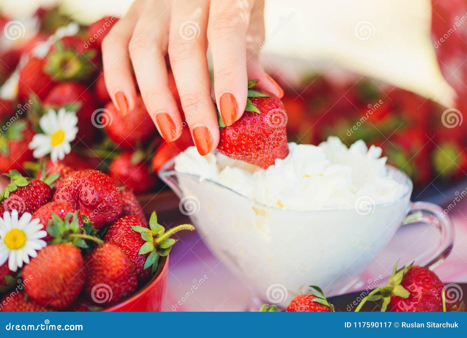Świeża truskawka z śmietanką w pucharze na stole w lato ogródzie dekoruje z chamomile kwiatami ręka bierze z lo