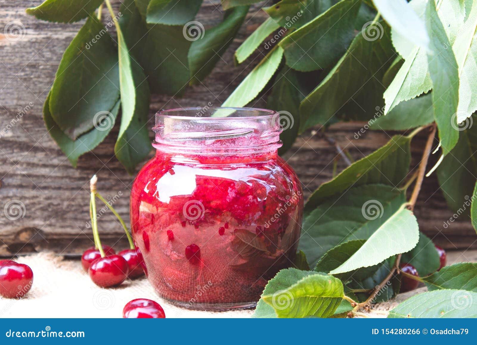 Świeża wiśni galareta z owoc na drewnianym tle blisko zieleń liści i jagod