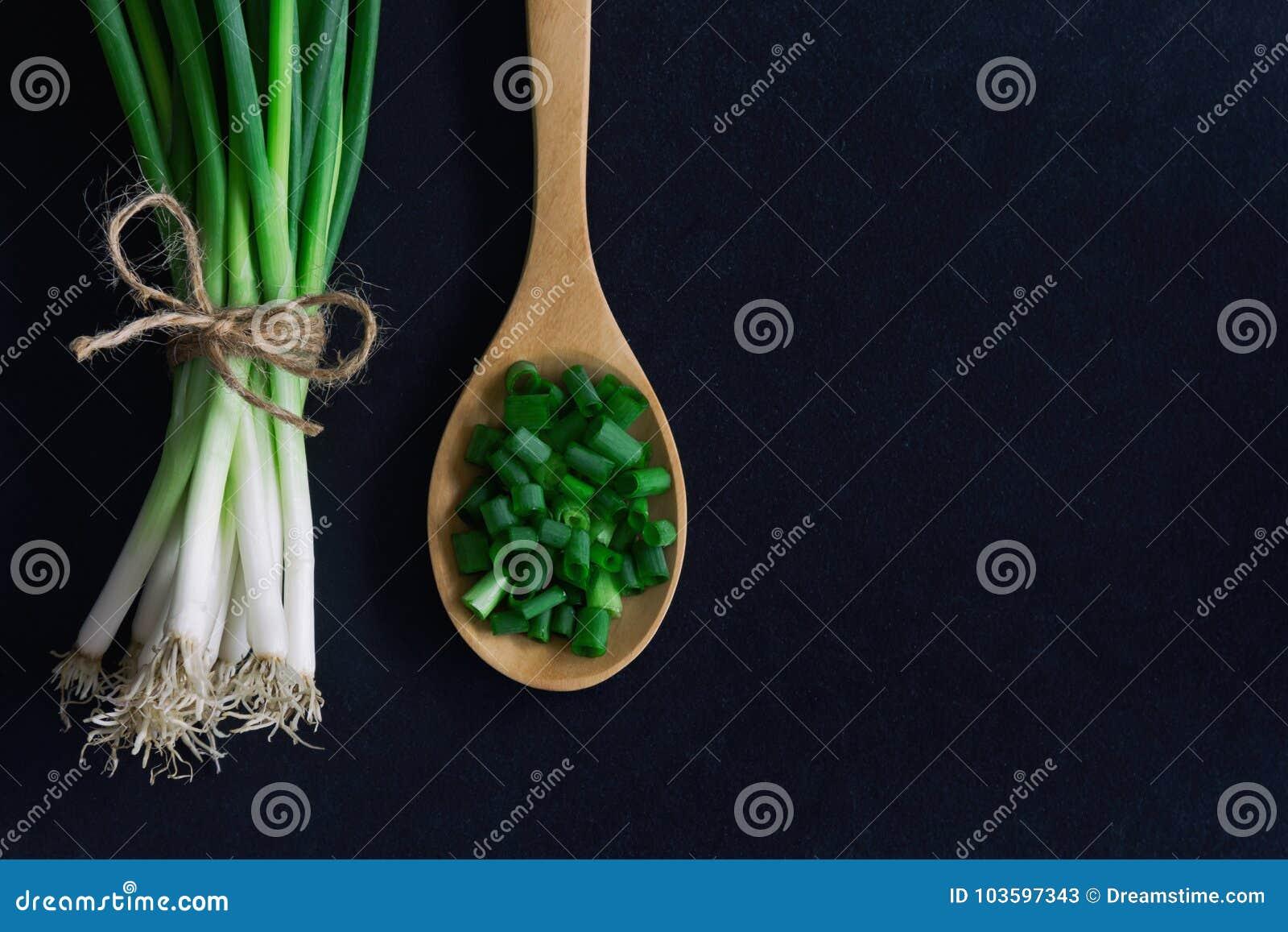Świeża wiosny cebula na czarnym granitu stole Zamyka up na siekającym c