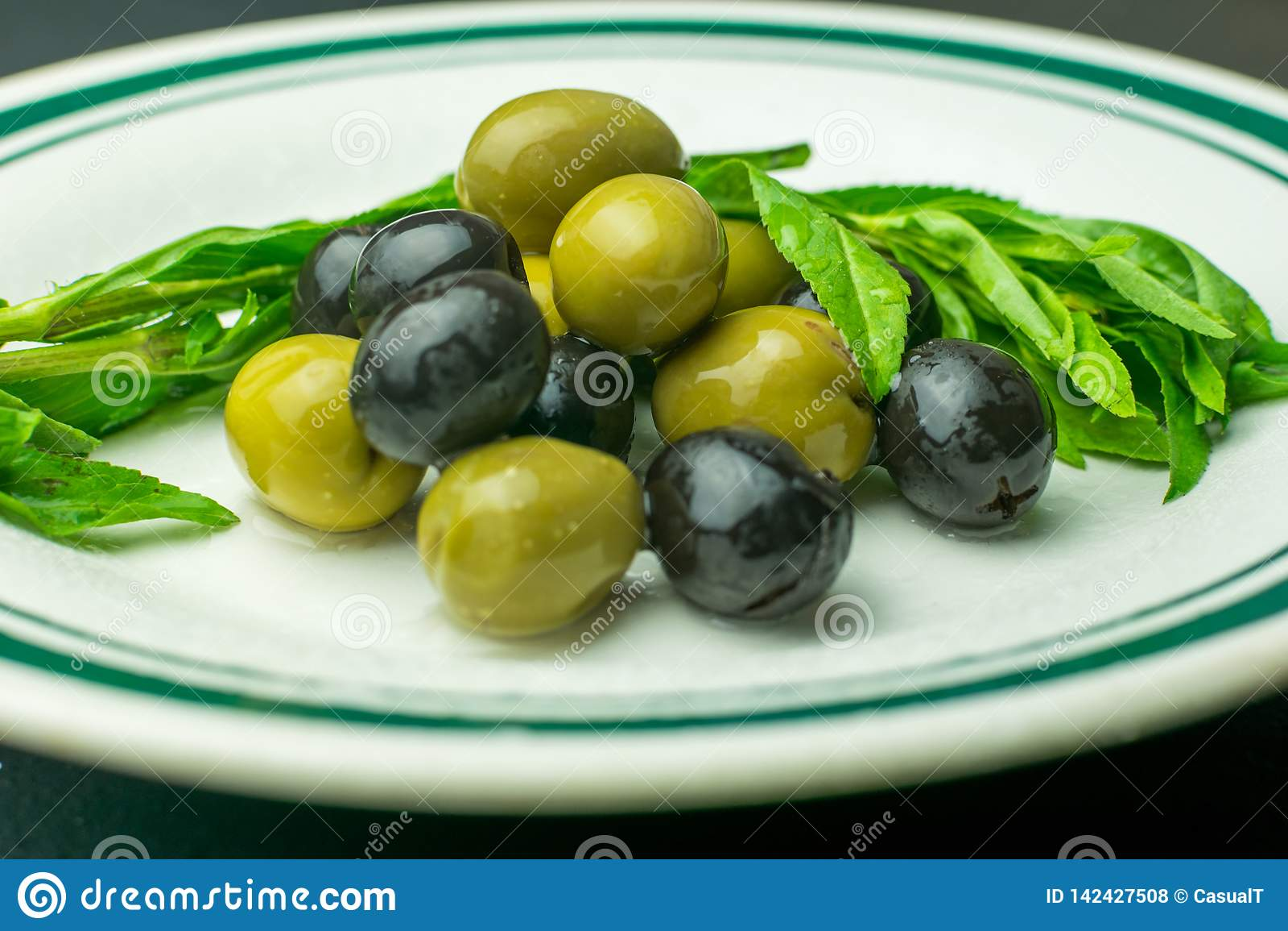 Świeża zieleń i czarne oliwki słuzyć na białym porcelana talerzu,