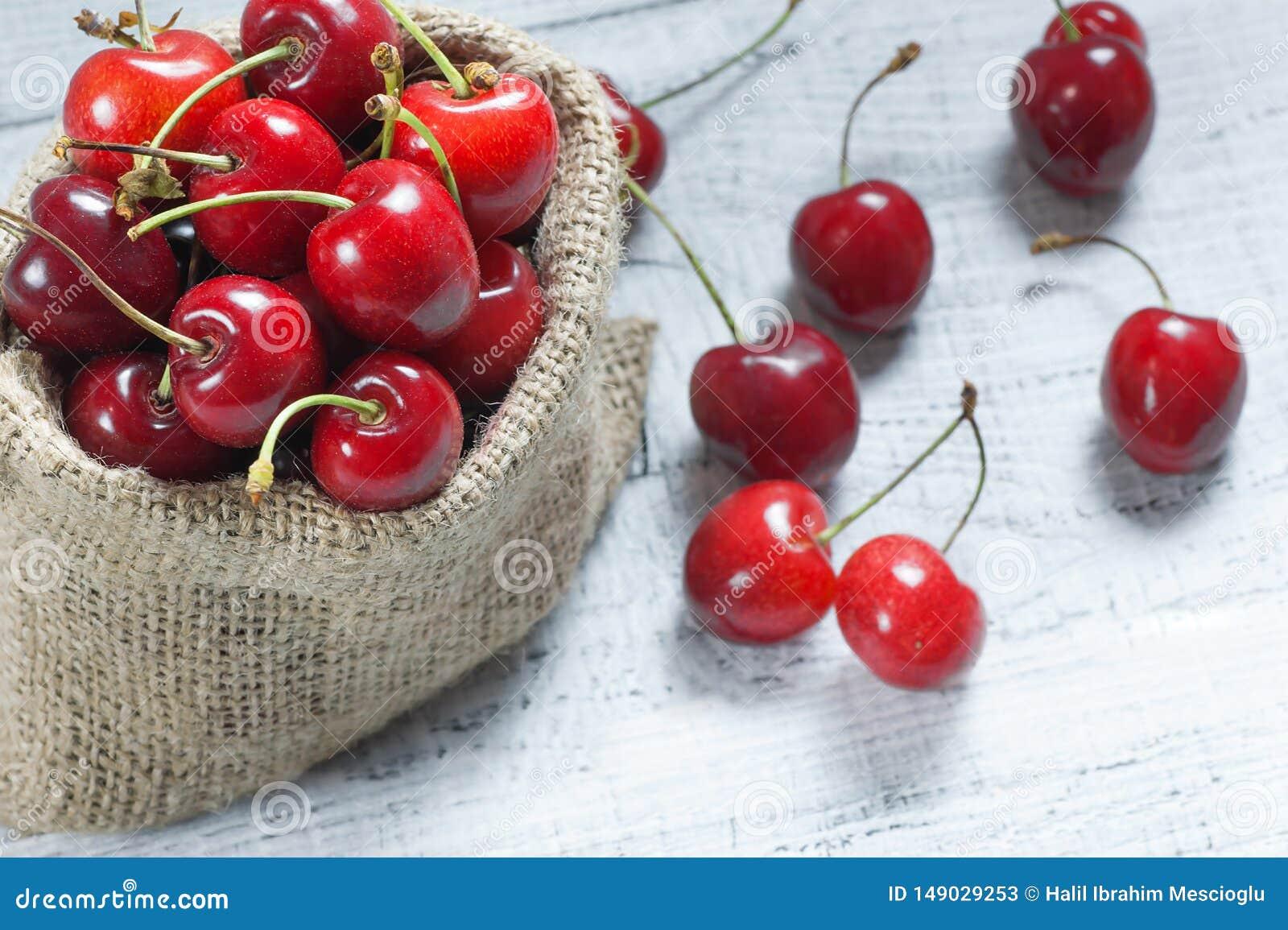 Świeże dojrzałe organicznie czerwone wiśnie w burlap grabiją na drewnianym tle