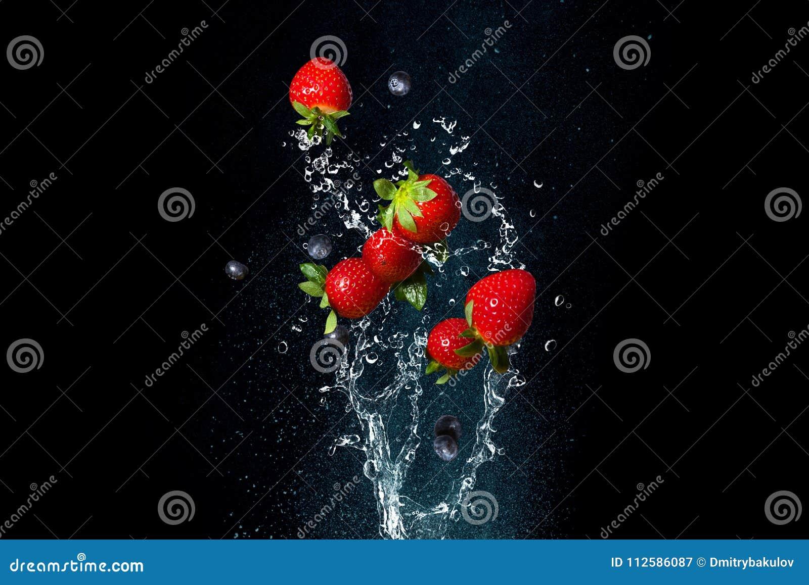 Świeże jagody w pluśnięciach woda na czarnym tle Soczyste truskawki