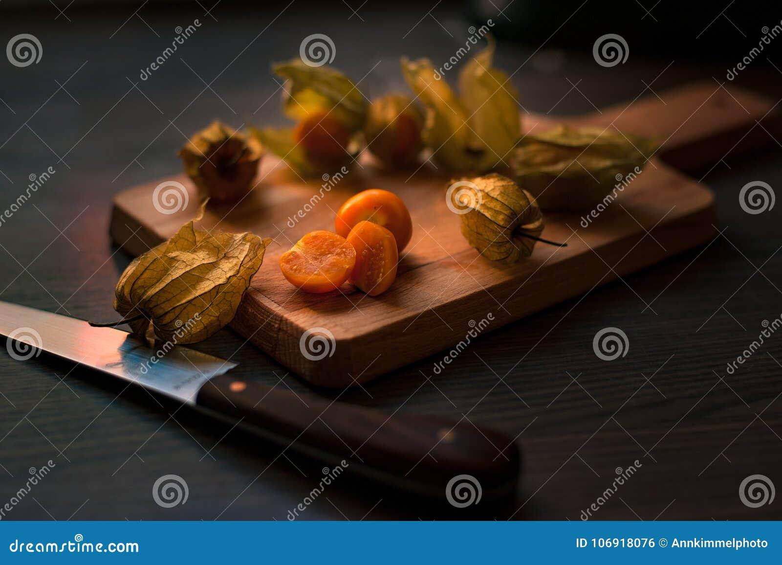 Świeże pęcherzyc jagody z przylądkami na drewnianej tnącej desce z