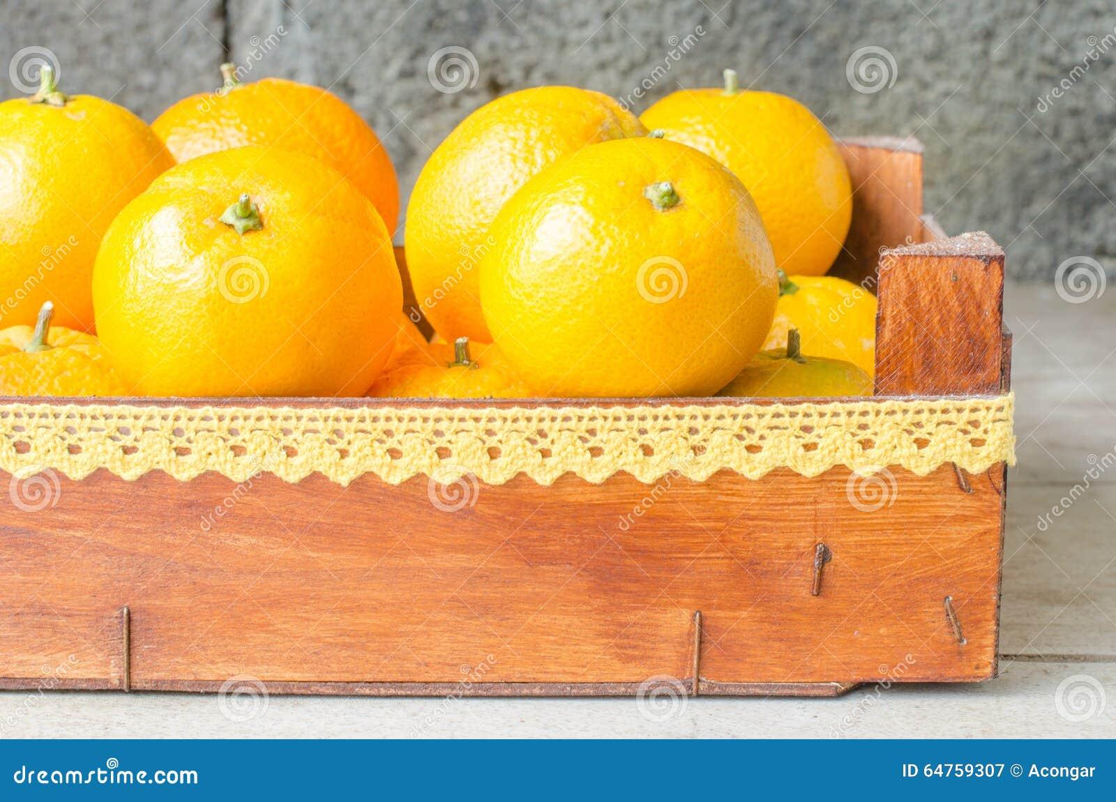 Świeże pomarańcze w drewnianym pudełku