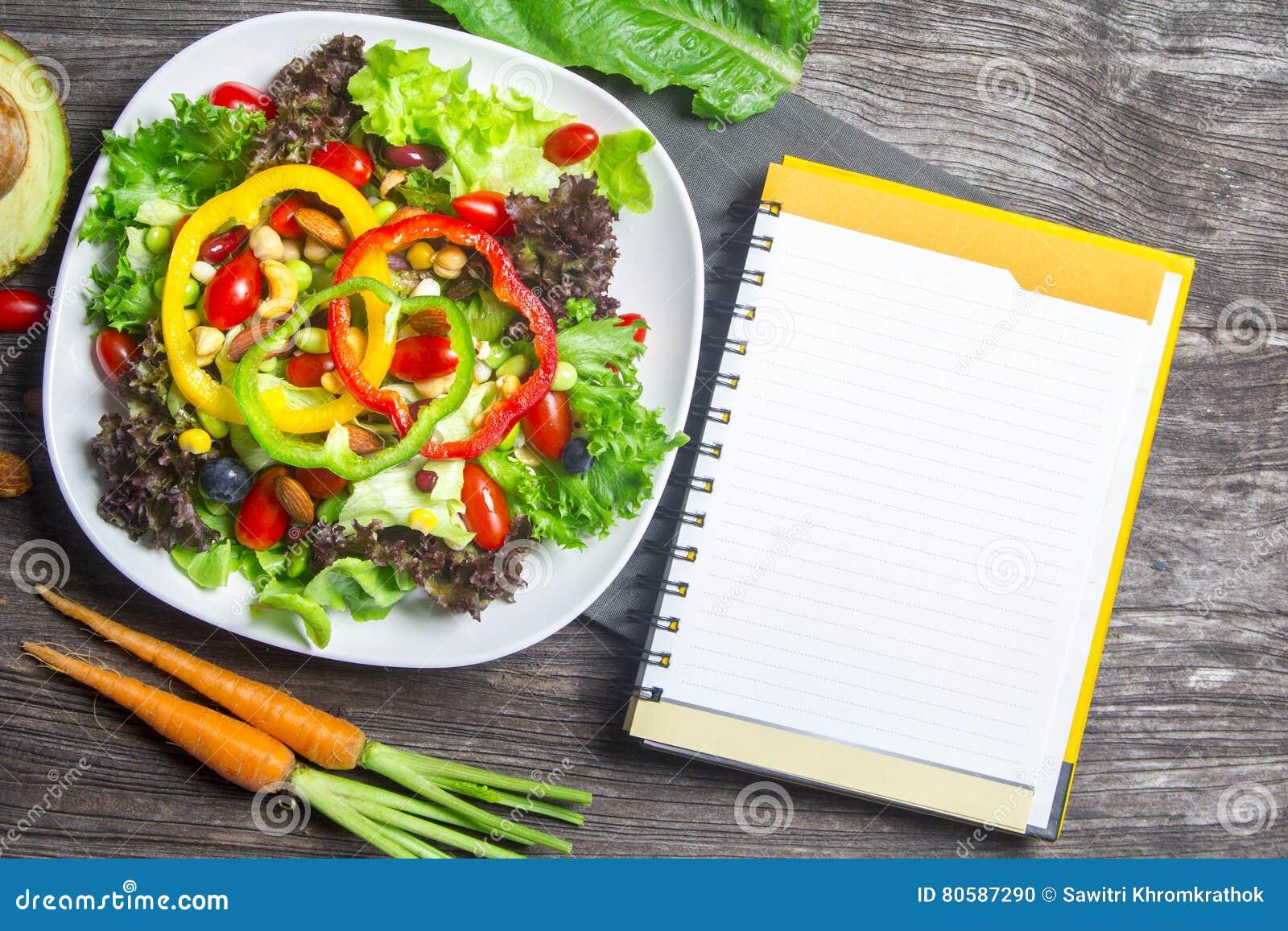 Świeżego warzywa sałatka z notatnika papierem na drewnie