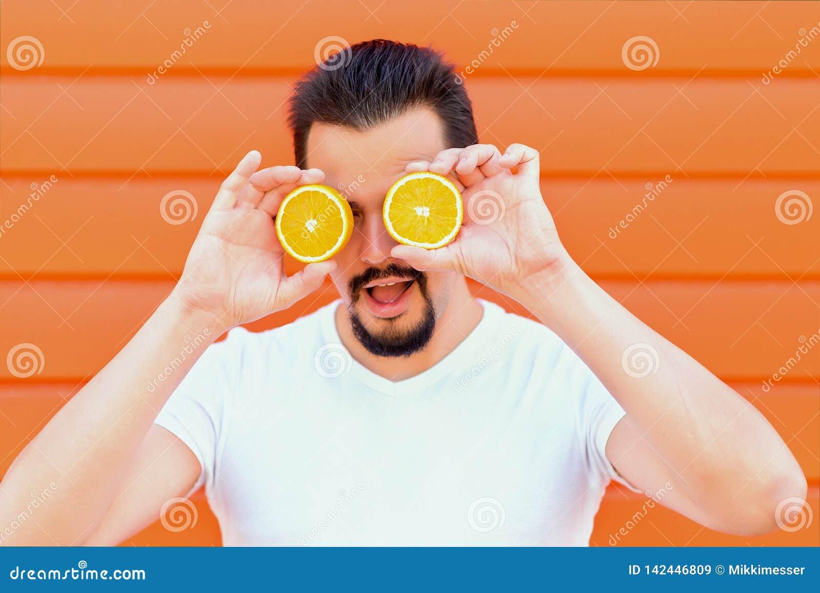 Świeżość i zdrowy styl życia: portret przystojny seksowny mężczyzna z brodą chuje oczy za pokrojonymi pomarańczami lubi okulary p