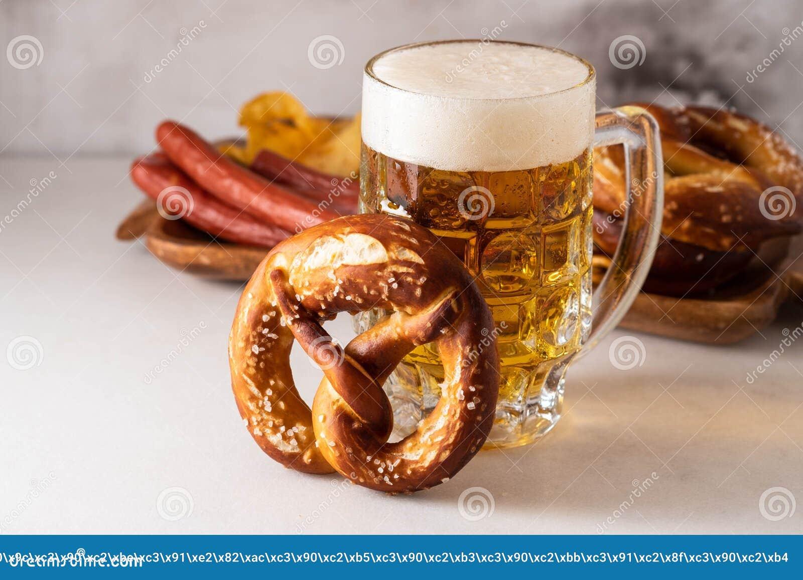 Świeżo piec domowej roboty miękki precel z solą na bielu stole z szkłem piwo
