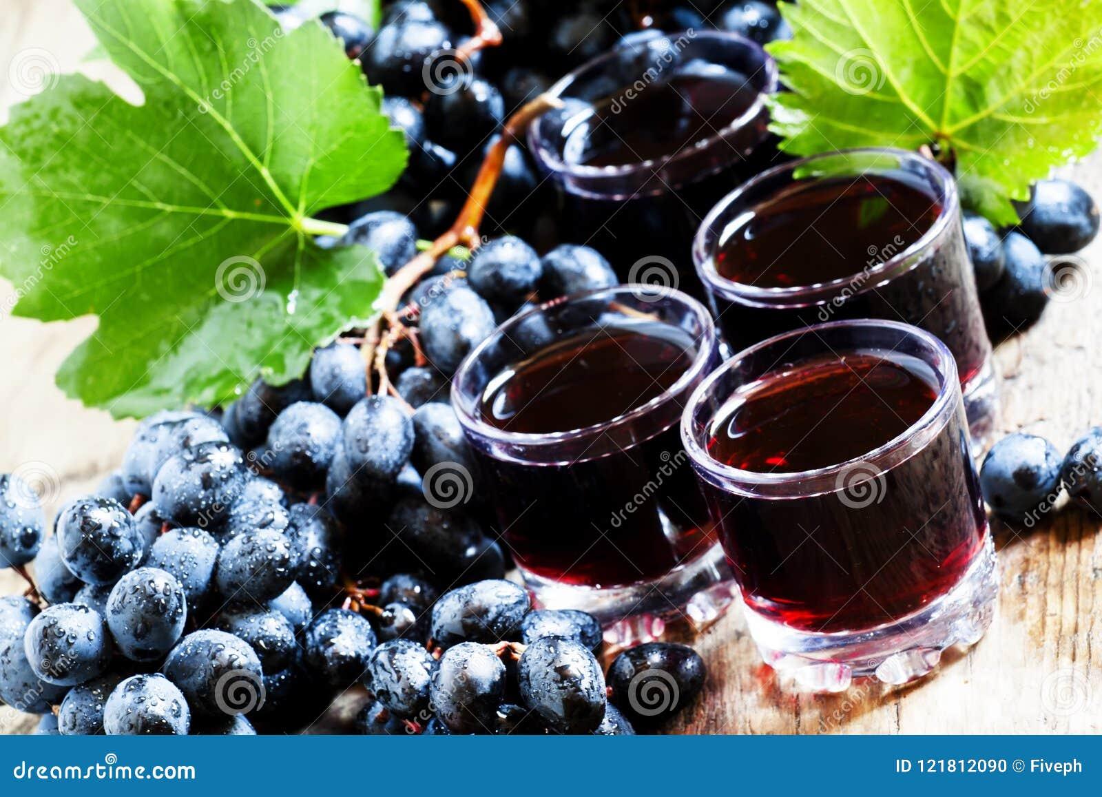 Świeży ciemny gronowy sok i świeże jagody na starym drewnianym stole, se