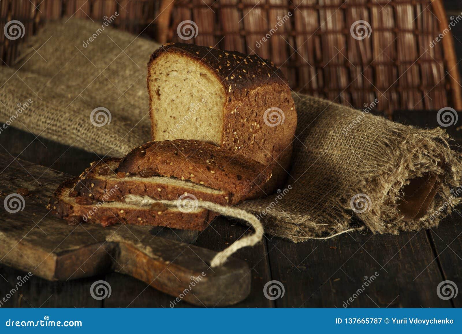 Świeży domowej roboty chleb z całym pszenicznym kolcem na czarnym drewnianym tle Świeży chleb z ucho banatka