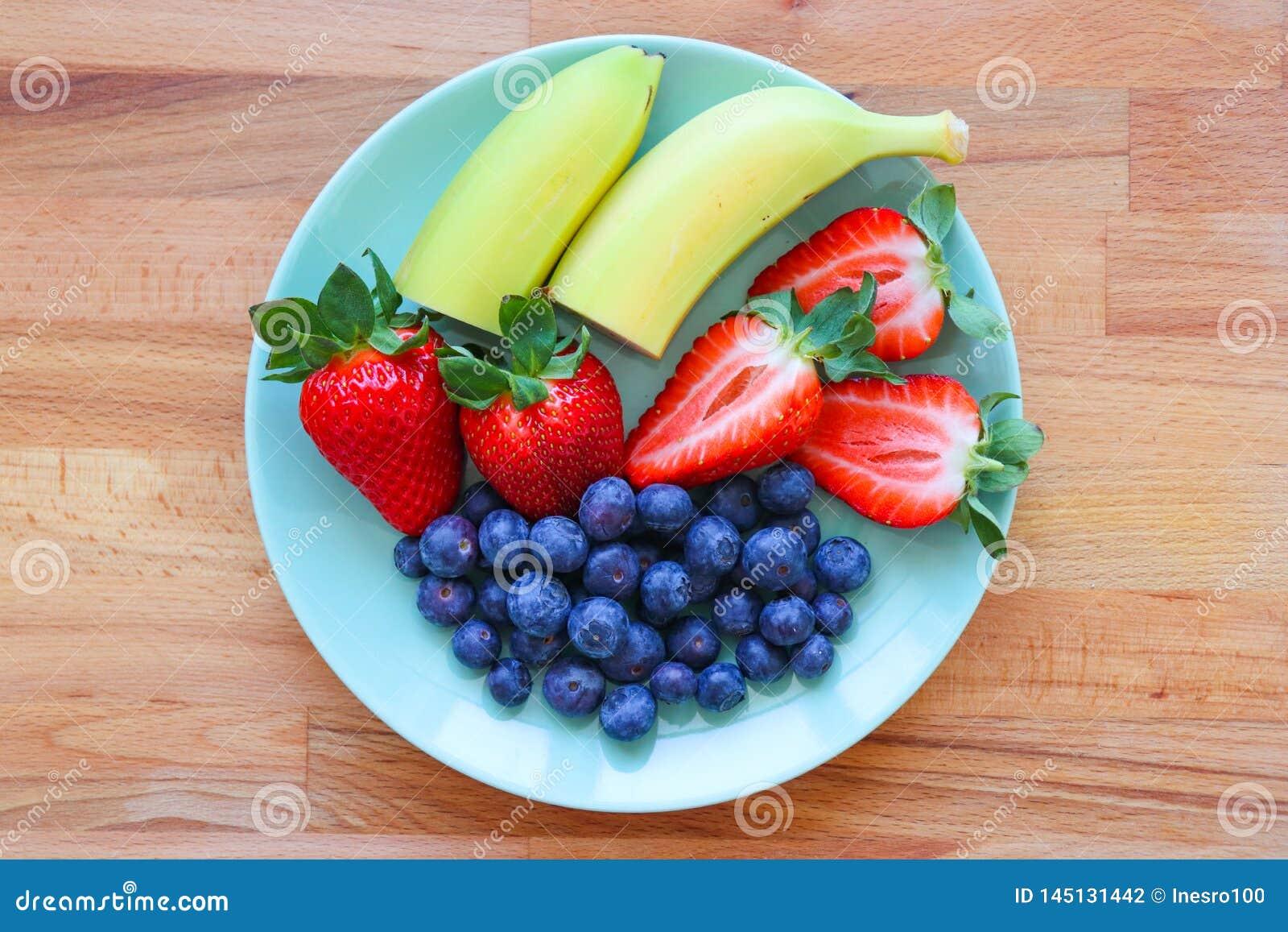 Świeży fruites talerz z bananami, truskawka, czarna jagoda